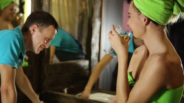 Instalatér s flirt s mladou holkou doma. muži s mladé zákaznici před sukničkář. dívka, která nosí osušku, drží sklenku bílého vína
