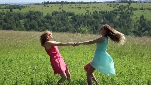 két fiatal barátnője körözött kéz a kézben a zöld rét