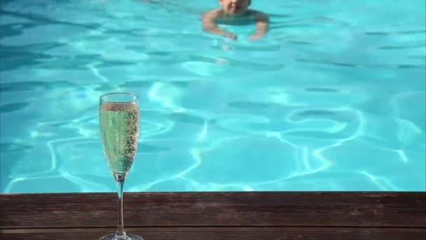 mladá šťastná žena pije šampaňské v bazénu