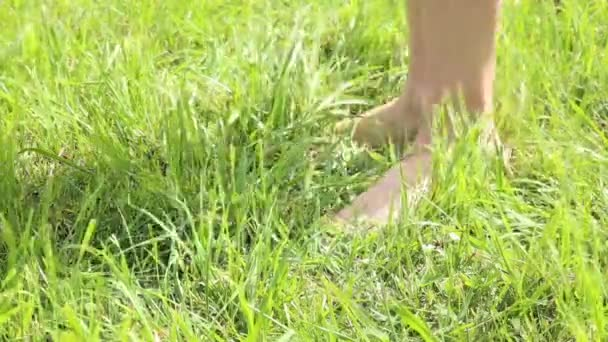 womans bare feet walking over green grass field, she throwing shoes on grass