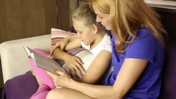 Mladá maminka čtení knihy nahlas své dceři, v obývacím pokoji na gauči před spaním