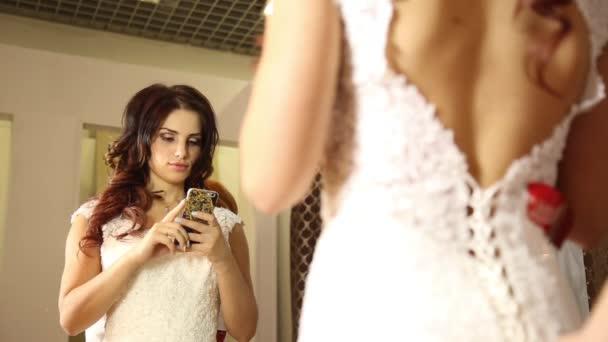 Il consulente aiuta la giovane donna di provare un abito da sposa. Ragazza felice di selezionato Abito da sposa. giovane sposa rende selfie sul tuo telefono