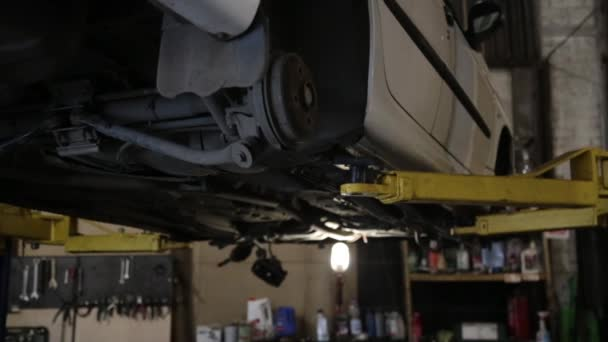 Lifting a car without rear-wheel on elevator in workshop of Service station