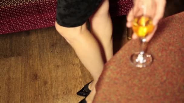 sexy žena nohy v černých šatech prochází kolem gauče a dá sklenku šampaňského na stůl