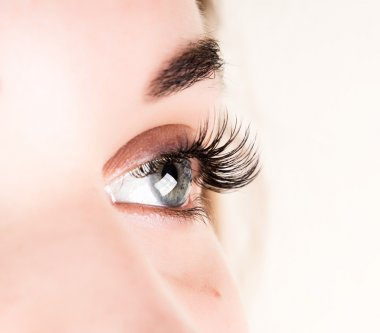 Beautiful young girl eyelash extension. Woman eye with long eyelashes. Beauty salon concept