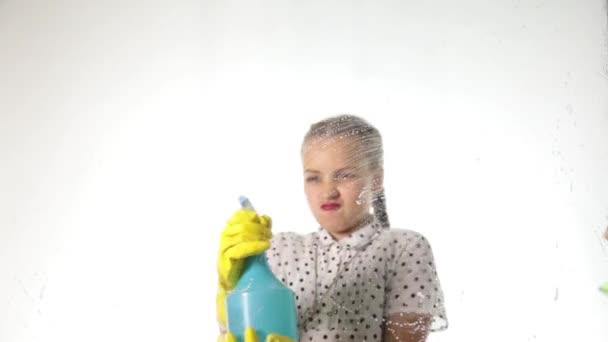 Lächelnde kleine Hausfrau wusch das Fenster mit einem Spray, Tuch und Waschmittel. Großes Glas aus Schaumstoff. Hausarbeitskonzept.