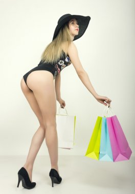 beautiful young lady in a bathing suit, big black hat on high heels, holding colorful bags. Girl goes shopping