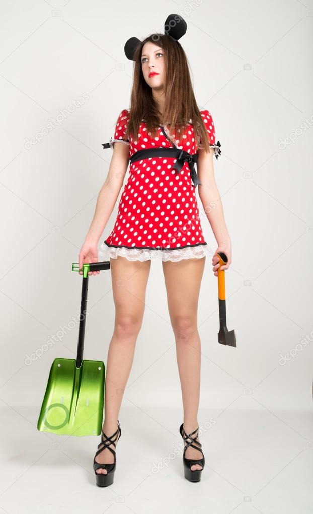 Busty beautiful young girl in a short dress with polka dots, bear in one  hand and a shovel in the other ax– stock image