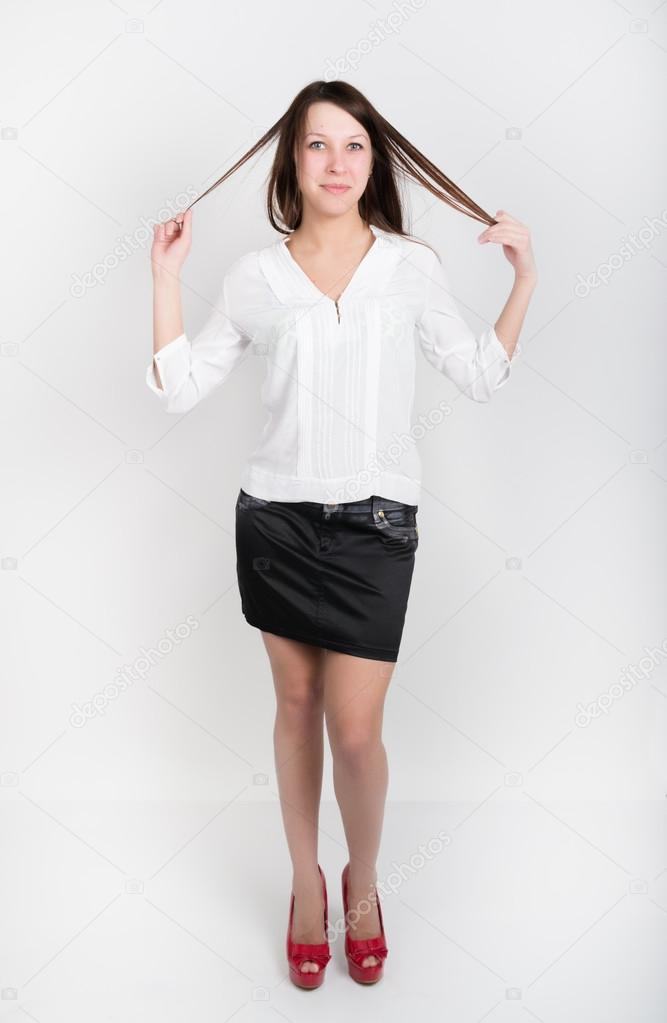 15d8d7ff2b Beautiful slim girl in a short black skirt, white blouse and red shoes with  high heels, holding his hair– stock image