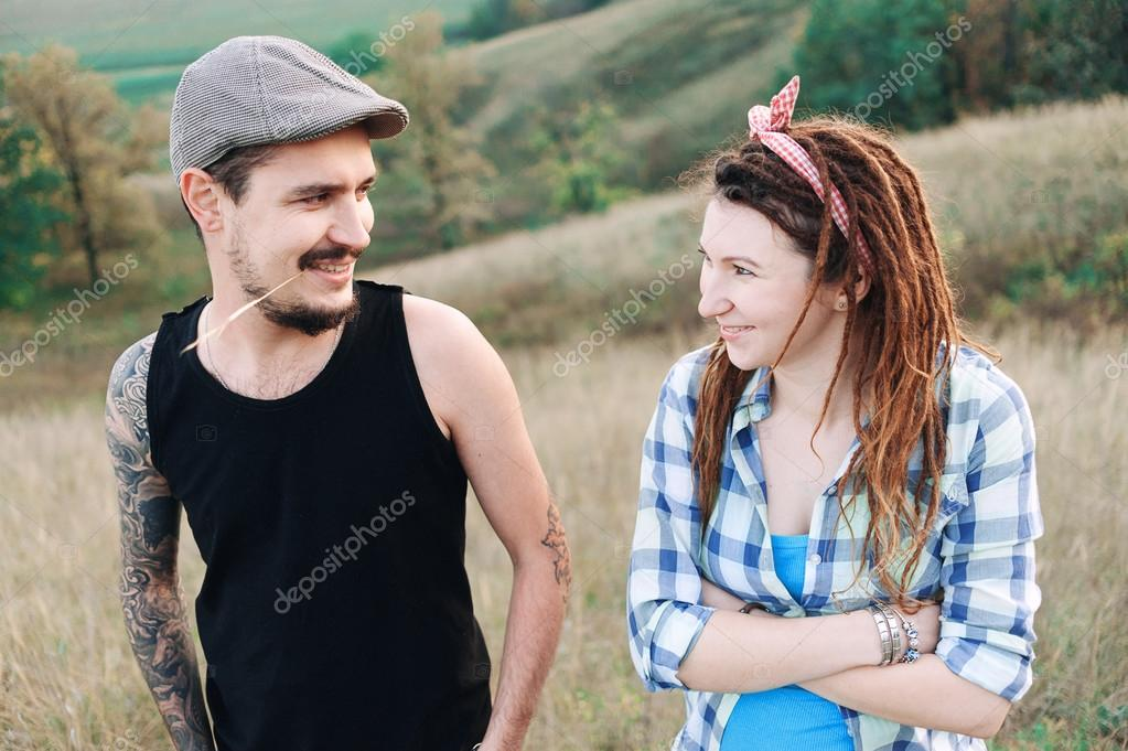 boy and girl, playing with dreadlocks, make each other mustache