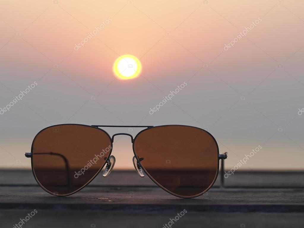 Closeup on eyeglasses with focused and blurred landscape sunset view