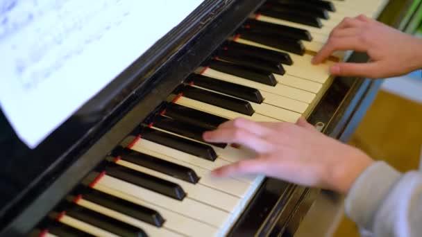 Zongorista kezek zongoráznak. Zenész művész játszani eszköz, Koncepció Zenei oktatás és előadás. Közelkép egy lány kezét játszik a zongorán