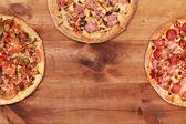 Three tasty pizzas on table