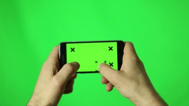 Muž rukou pomocí chytrého telefonu pro psaní textových zpráv s chroma klíč, zelená obrazovka
