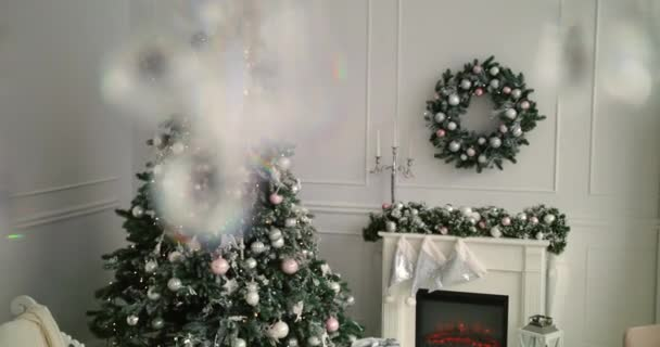 Christmas tree decorations in the room. Amazing flashing garland radiating christmas spirits and mood. Room with christmas and new year interior decoration. Green tree decorated with