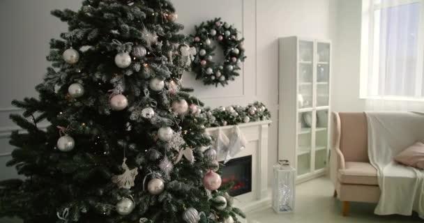 Karácsonyfa dekoráció a szobában. Csodálatos villogó koszorú sugárzó karácsonyi szellemek és hangulat. Szoba karácsonyi és újévi belső dekorációval. Zöld fa díszített