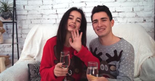 Attraktives Mädchen mit Freund winkt in die Kamera, sitzt mit Brille in der Hand auf dem Sofa