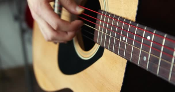 Strumming a guitar close up in super slow motion 300fps