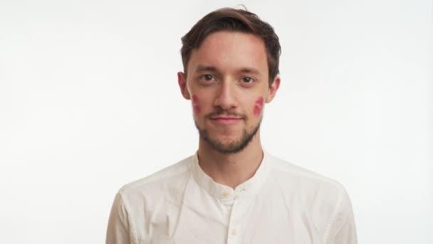 Junger kaukasischer Mann mit dunkelbraunen Haaren, Bart, roten Lippenstiftabdrücken oder Flecken auf den Wangen lächelt, zwinkert. Nahaufnahme Porträt von sexy attraktiven Kerl isoliert auf weißem Wandhintergrund. Liebhaber