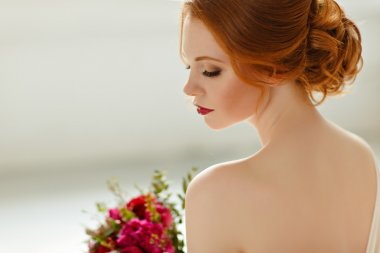 The refined portrait of red-haired girl in profile with a bouque