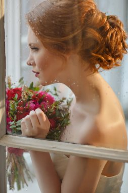 Very pretty sophisticated red-haired girl with a bouquet in his