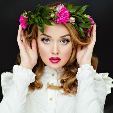 Portrait of a beautiful sensual glamorous yellow-haired girl in a white blouse with a wreath of flowers on his head, in the Studio on a dark background, close up