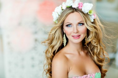 Very beautiful and sensual blonde girl, smiling, with a wreath o