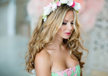 Very beautiful sensual girl with curly blond hair and a wreath o