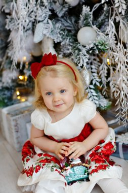 Little baby girl charming blonde in a red dress sitting beside a
