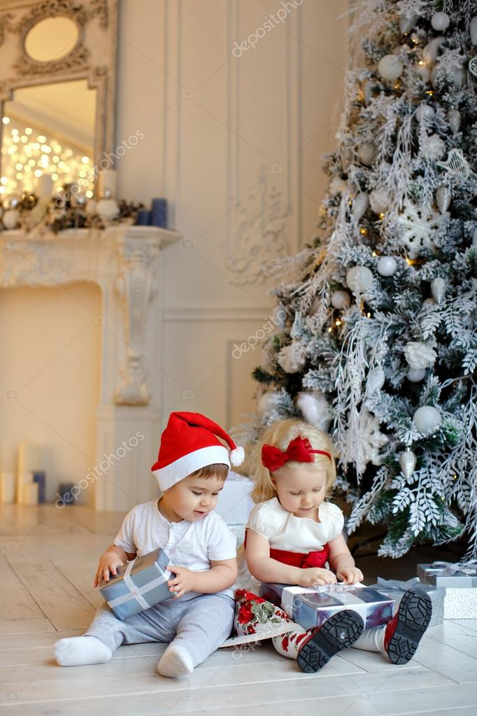 Small charming baby boy in red Santa hats and the little blond g ...