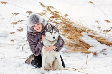 The girl in the gray coat smiling next to a grey husky dog in winter background yellow reeds