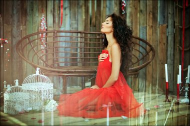 Sexy sensual very beautiful curly girl in a red dress sitting on