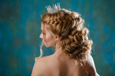 Portrait of a young blonde woman with luxury thick hair, braided into a braid, wearing a white dress and a crown on her head, like a princess, view from the back