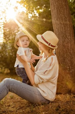 Slender beautiful blonde mom in jeans, a beige shirt and a hat holding a baby boy on the background of the Park at sunset and smiles