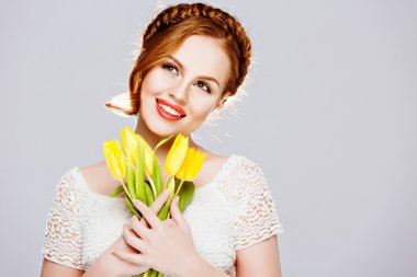 Beautiful girl with red hair in a braid, holds yellow tulips with closed eyes on white background in Studio