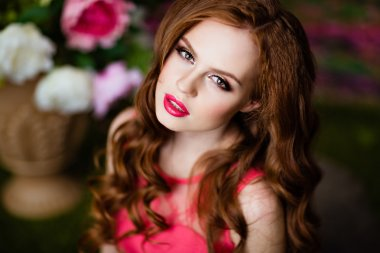 Portrait of a sensual sexy redheaded girls on floral background