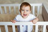 Malý roztomilý roztomilý blonďatý chlapeček v pruhovaném bodykit je v dětském pokoji s bílou postýlku a smích