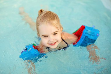 Adorable little girl blonde swimming in the pool with armbands a