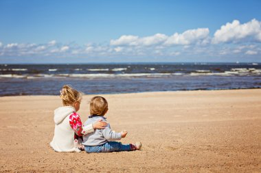 Older sister and younger brother sitting in sweaters on the beach, cuddling, against the sea and clouds