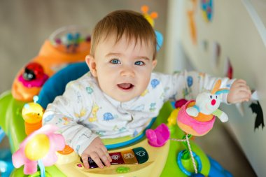 Little baby boy sitting in a colourful baby Walker with toys and smiling at home in the nursery, close-up