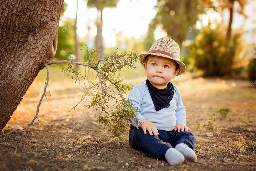 Little adorable baby boy in a straw hat and blue pants sitting with