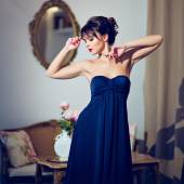 Schöne Brünette Mädchen in einem blauen Kleid stehen im Innenraum
