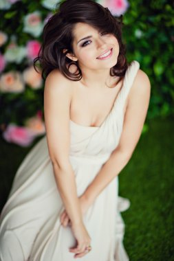 Very beautiful girl brunette in a beige dress smiling and happy