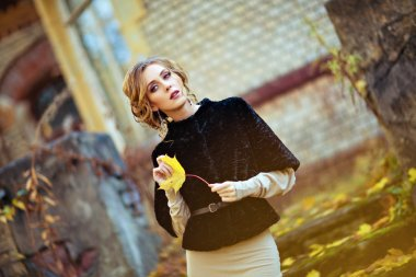 Portrait of a sensual kinky girl in the black coat with the shee