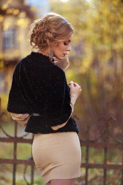 Portrait in profile of a sensual kinky girl in black coat autumn