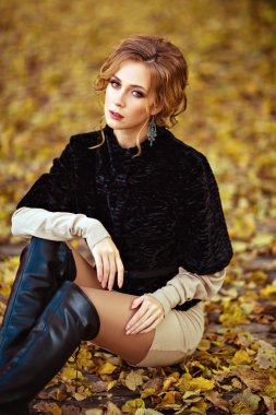 Portrait of a sensual kinky girl in the black coat in the fall,