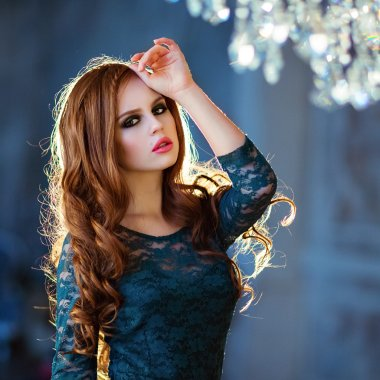Beautiful red-haired curly girl in a green dress on a blue backg