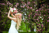 Fotografie Very beautiful happy bride blonde curly hair in a white dress, a