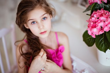 Portrait of cute baby girls with gorgeous hair in a pink dress i