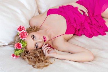 Beautiful slim sexy blonde in a red dress and a wreath of flower